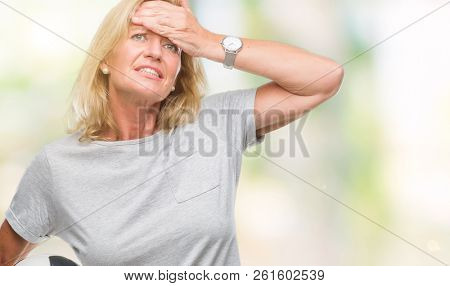 Middle age blonde woman holding soccer football ball over isolated background stressed with hand on head, shocked with shame and surprise face, angry and frustrated. Fear and upset for mistake.