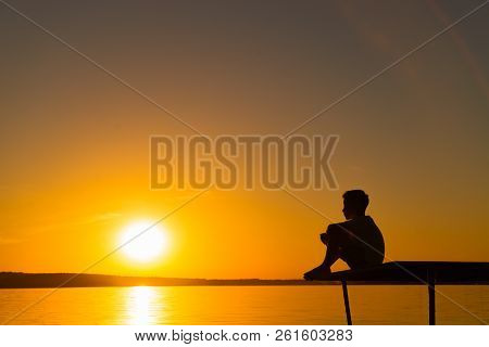 the little kid sits on a bridge and looks on the river on the background at sunset. A boy is relax near the lake poster