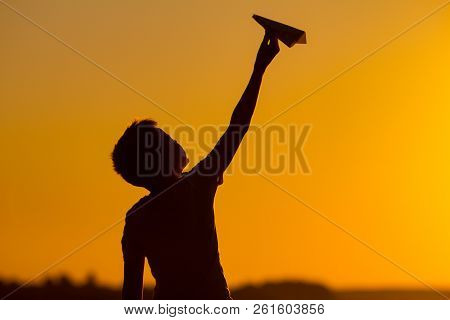 Little Boy Holds A Paper Airplane In His Hand At Sunset. A Child Raised His Hand Up To Sky And Plays
