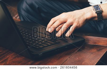 A Man's Hand With A Wrist Watch Stands On The Laptop's Touchpad. Businessman Works At Home In His Ow