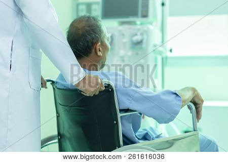 Asian Patient In Wheelchair Sitting In Hospital Corridor With Asian Male Doctor, Medical Equipment C