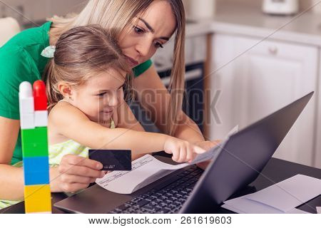 Financial Issues - Young Mother Calculating Finances At Home With Cute Daughter