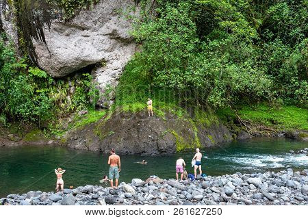 French Polynesia, Tahiti-- March 18, 2018. Tourists On A Hike Through A Rain Forest Go For A Swim In