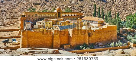 The medieval citadel is the Sacred Monastery of the God-Trodden Mount Sinai (St Catherine's), located in desert gorge, at mountain foot, surrounded by tall ramparts and monastic garden, Sinai, Egypt. poster