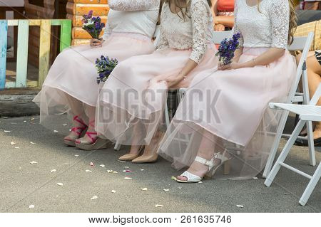 Bridesmaids With Bouquet Of Flowers On The Ceremony. Row Of Bridesmaids With Bouquets At Wedding Cer