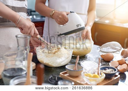 Unrecognizable Women Making Cookie Dough In Kitchen, Using Whisk And Modern Electric Mixer While Bea