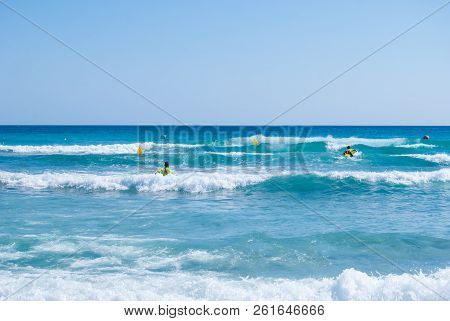 Lifeguards Running In The Middle Of A Rough Sea One  With Yellow Surfboard The Other By Foot