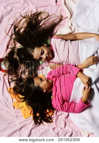 Schoolgirls In Pink Pajamas Wallow On Colorful Pillows, Top View