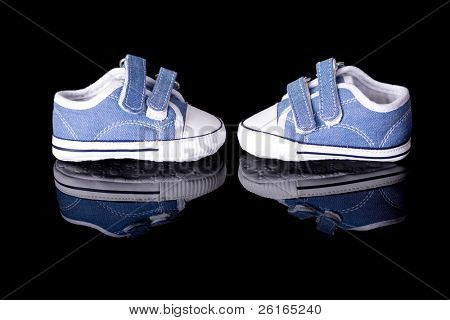 pair of new little blue baby shoes, newborn or pregnancy concept, studio shoot isolated on black with reflection