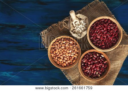 Assortment Of Kidney Beans In Wooden Dishes And White Kidney Beans In Linen Bag On Dark Blue Wooden