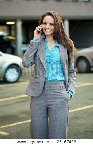 young very attractive businesswoman talks over her mobile phone, blurred car as background, outdoor shoot