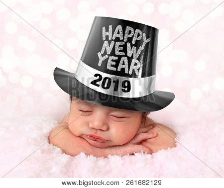 Newborn baby girl wearing a Happy New Year hat. 2019