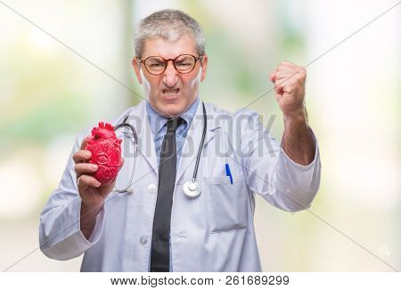 Handsome senior cardiologist doctor man holding heart over isolated background annoyed and frustrated shouting with anger, crazy and yelling with raised hand, anger concept