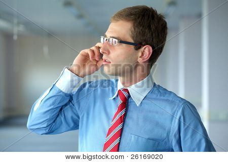 young confident businessman in blue shirt and red tie talks over mobile phone in his office