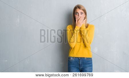 Beautiful young woman standing over grunge grey wall shocked covering mouth with hands for mistake. Secret concept.