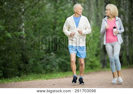 Happy active senior couple jogging in park among green trees in the morning