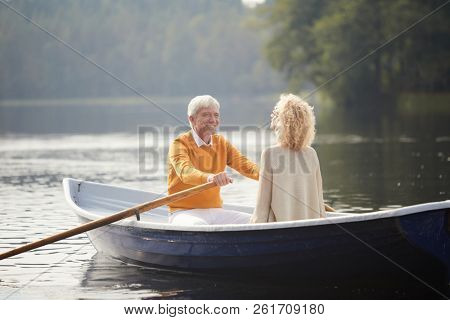 Cheerful excited affectionate senior man in yellow sweater falling in love with beautiful curly-haired lady rowing boat and smiling at girlfriend while enjoying date on boat.