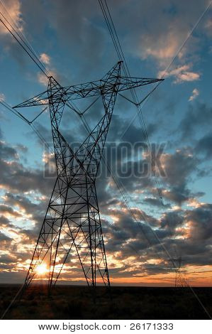 View of power lines with sunset and clouds in background