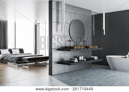 Interior Of Master Bedroom With A Bathroom Next To It. Gray Walls, Concrete And Wooden Floor. Luxury