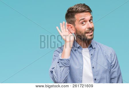 Young handsome man wearing white t-shirt over isolated background smiling with hand over ear listening an hearing to rumor or gossip. Deafness concept.