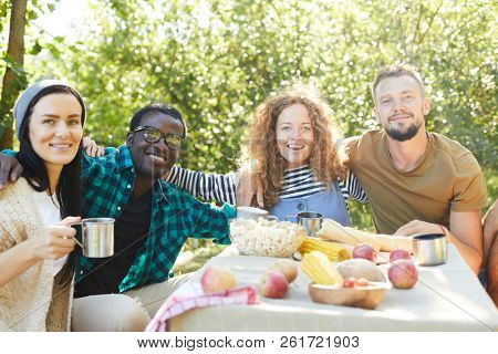 Group of young cheerful trippers in activewear gathered by served table in natural environment