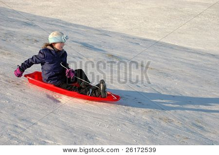One little girl sledding on a winter day in a red sled
