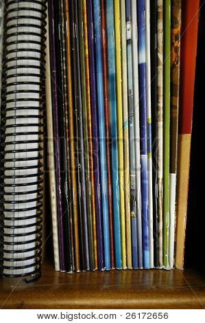 Closeup of a stack of many colorful magazines on a shelf