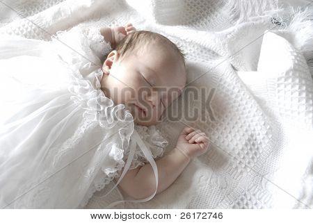 New born Babymädchen gekleidet in weiß schlafend auf einer weißen Decke