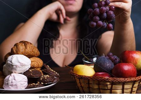Obesity prevention, conscious eating, nutrition choices, mindfulness and healthy lifestyle. Cropped portrait of overweight woman choosing between junk sweet food and fruits poster