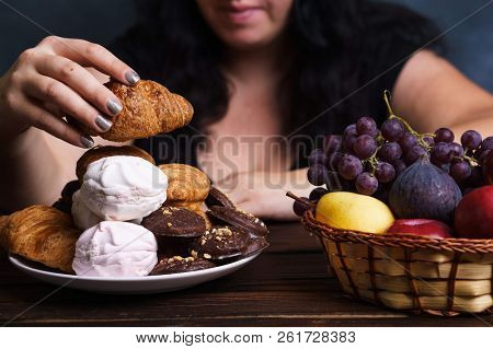 Sugar addiction, nutrition choices, conscious eating, overeating. Cropped portrait of overweight woman choosing between junk sweet food and fruits poster