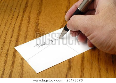 Person writing thank you note with pen on card