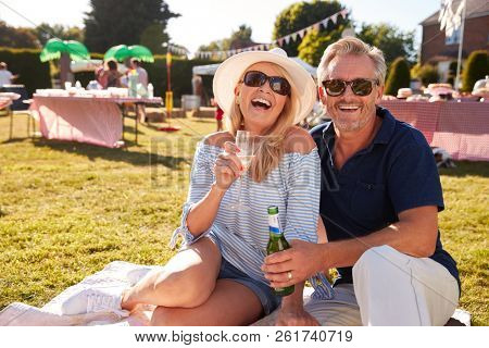 Portrait Of Mature Couple Sitting On Rug At Summer Garden Fete With Drinks