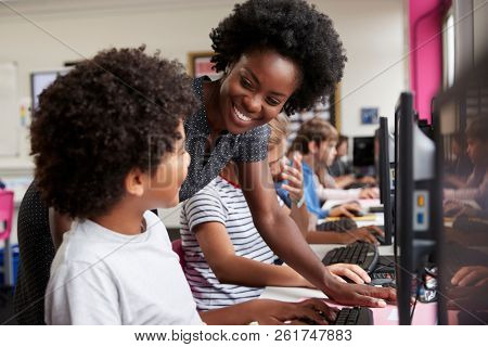 Teacher Helping Male Pupil Line Of High School Students Working at Screens In Computer Class