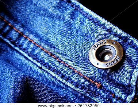 Vibrant Blue Close Up Image Of Waistband Of Denim Jeans With Double Stitching And Metal Tack Button