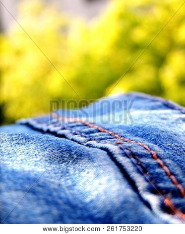 Vibrant Close Up Image Of A Blue Denim Jeans Under Bright Sunlight With Blue Brown Double Stitching