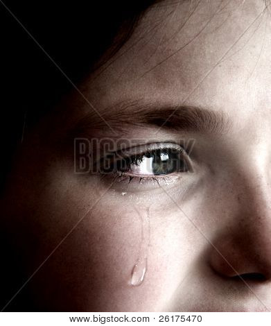 Closeup of girl crying with tear rolling down her cheek