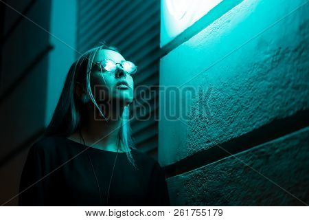 Millennial enigmatic pretty girl with unusual dyed hairstyle near glowing neon wall at night. Blue hair, golden sequins as freckles, nose piercing. Mysterious hipster teenager in glasses poster