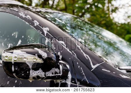 Car Wash With Soap.car Washing Process Of Luxury Black Car Full Covered With White Foam And Bubbles.