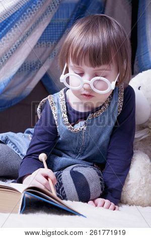Cute little child girl reading a magic book with teddy bear before bedtime (sleep, health, childhood, toys concept) poster