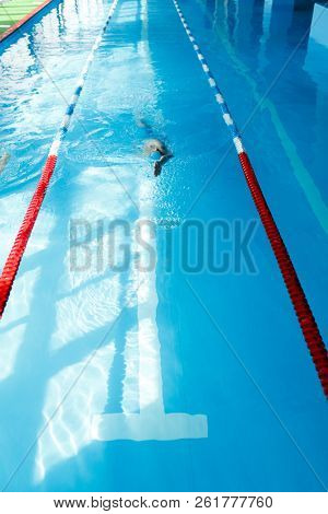 Photo of young athlete man in blue cap swimming on back in swimming pool
