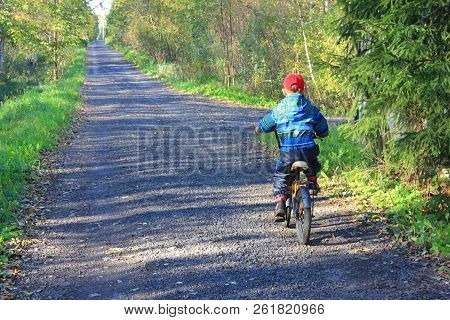 Unidentified Young Boy Riding Bike Outdoors Alone On Rural Road. Child Biking On Countryside Empty L