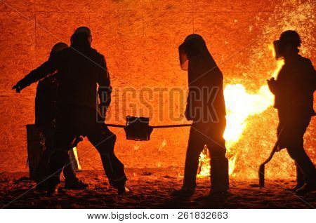Group of workers steelworkers. Metal casting. Production of metal.