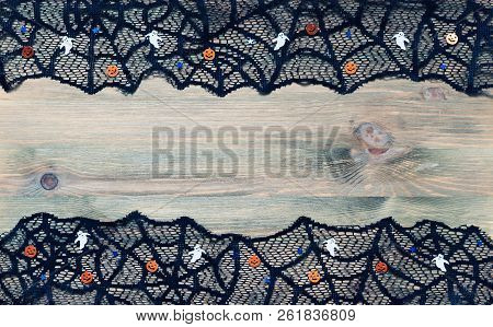 Halloween background. Halloween decorations aand black lace cobweb on the dark wooden background with free space for Halloween text