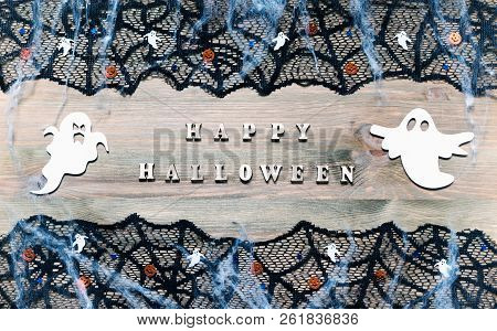 Halloween festive background. Happy Halloween letters and Halloween decorations on the dark wooden background