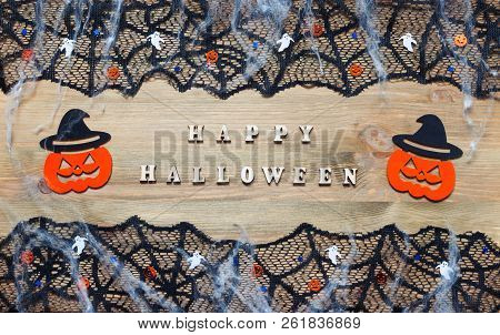 Halloween background. Happy Halloween letters and Halloween decorations on the dark wooden background