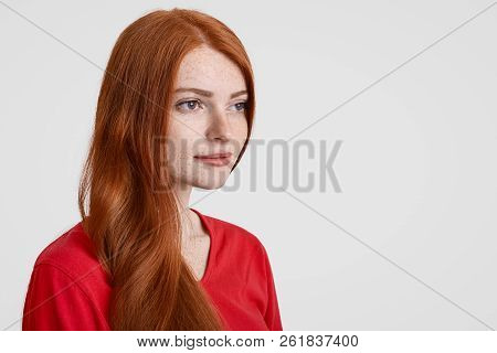 Sideways Shot Of Beautiful Red Haired Freckled Woman With Long Hair, Thinks About Something, Focused