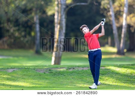 Young golf player hits a driver shot from the tee on a golf course. Concept: competition, concentration, sport, wealthy life.