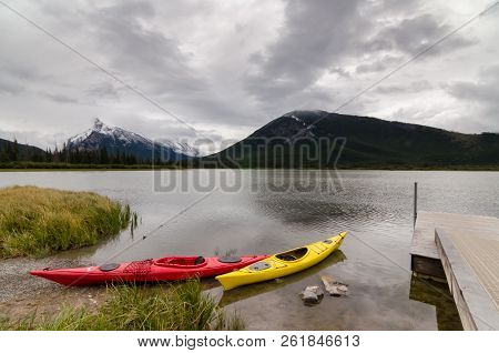 Red and yellow kayaks sitting by a dock with a view of Mount Rundle on Vermilion Lakes in Banff National Park, Alberta, Canada