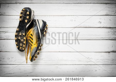 Old football shoes hanging on wooden wall