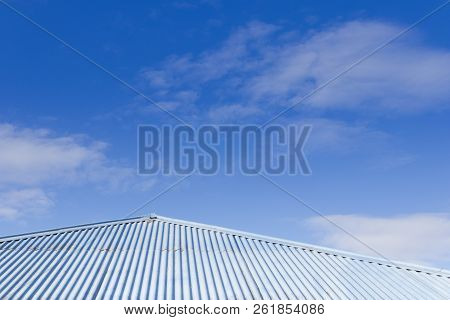 Blue Tin Corrugated Tin Roof With Blue Sky In The Background. Sunny Day.